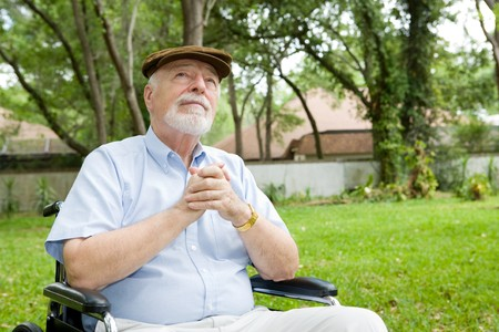 Senior man in wheelchair praying, in a beautiful outdoor setting.