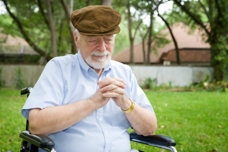 Senior man in a wheelchair making a tearful prayer to God. Stock Photo - 4136740