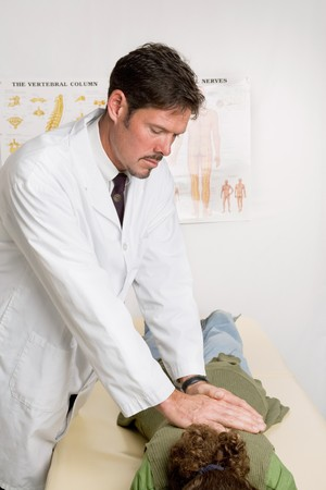 spinal adjustment: Handsome chiropractor adjusting a female patient in his office.   Stock Photo