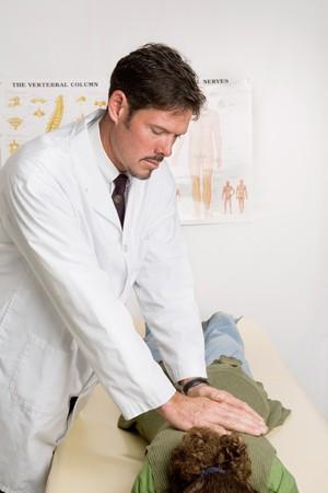 spinal manipulation: Handsome chiropratico adegua una donna paziente nel suo ufficio.