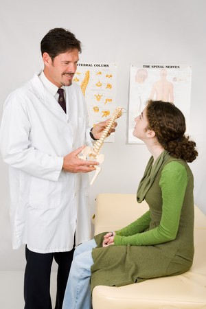 Chiropractor discussing treatment options with a patient.   photo