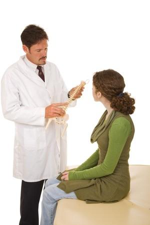 spinal manipulation: Chiropratico spiegando la spina dorsale di un nuovo paziente. Isolato su sfondo bianco.