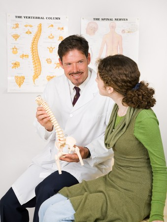 spinal manipulation: Friendly, smiling chiropractor uses a model to explain the spinal nervous system to a patient.