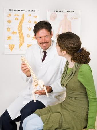 spinal manipulation: Friendly, sorridendo chiropratico utilizza un modello per spiegare la colonna vertebrale del sistema nervoso ad un paziente.
