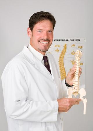 spinal manipulation: Handsome chiropratico azienda plastica replica di un colonna vertebrale.