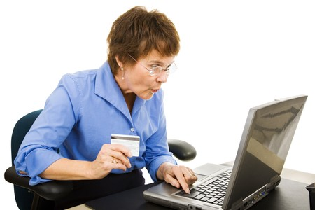 goofing: Mature woman finds a bargain shopping online.  Isolated on white.