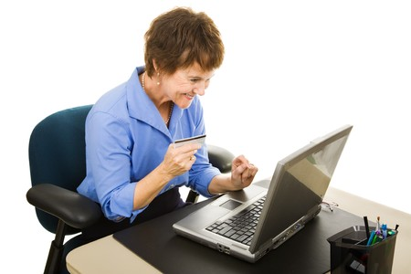 Businesswoman shopping online while at work.  Isolated on white.