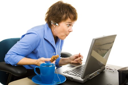 Office worker snacking and browsing the internet, shocked by what shes seeing.  Isolated on white.   photo