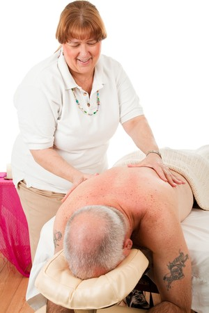 Happy massage therapist treating a male client. Isolated on white.