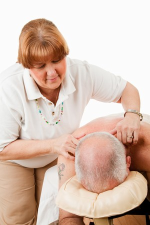 back rub: Massage therapist works on relieving tension in her clients shoulders.