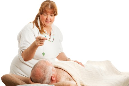 New age healer using a jade pendulum to unblock her patient's energy centers. Stock Photo - 4193178