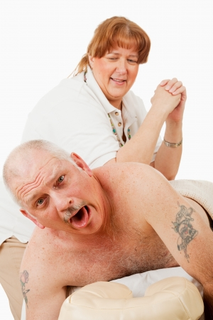 back rub: Humorous photo of a man surprised by a painful massage from an overly enthusiastic masseuse. Stock Photo
