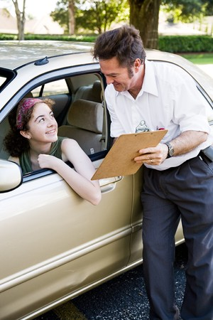 Driving instructor showing a teen driver the results of her test.   版權商用圖片