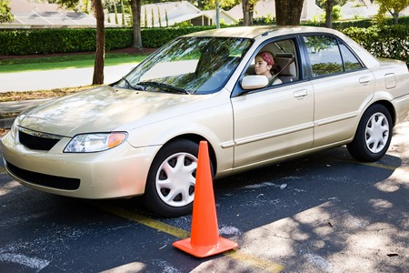 Tiener meisje leren parallel parkeren van een auto. Stockfoto