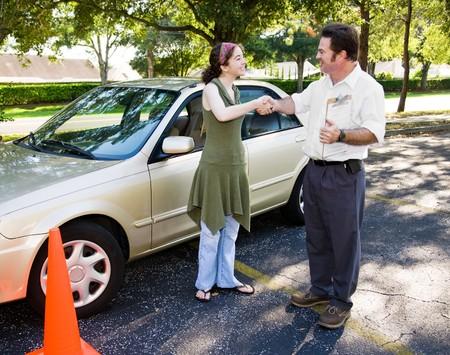 Rij-instructeur feliciteert tiener student op het passeren van de drivers test.