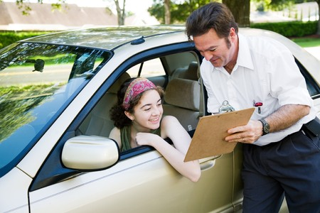 woman driving car: Teen girl reviews her score on the driving test with the instructor.