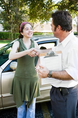 Teen girl getting a handshake from her driving instructor.   photo