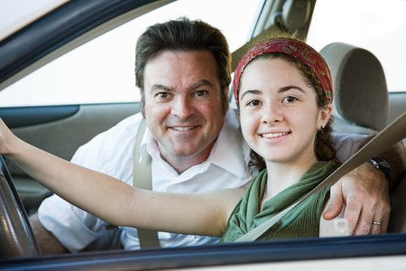 man driving: Teen girl gets driving lessons from her proud father.