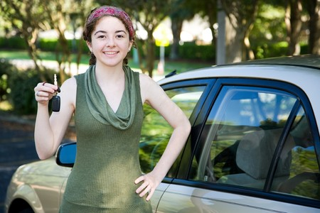 Pretty teen girl holding up the keys to her new car. Stock Photo - 4210210