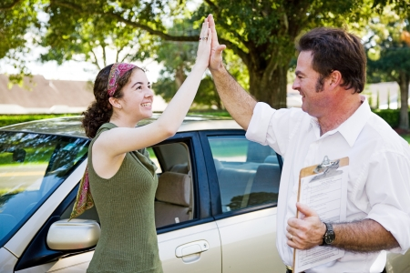 pass test: Teen girl passes driving test and gets a high five from her instructor.