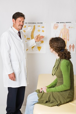 Chiropractor using *generic* charts to explain the spinal column to a patient. Stock Photo - 4254117