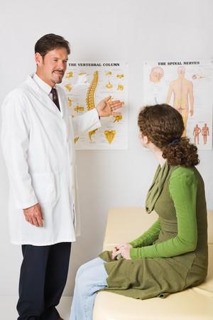 spinal manipulation: Chiropratico utilizzando * * generico grafici per spiegare la colonna vertebrale di un paziente.