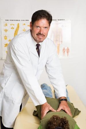 spinal manipulation: Chiropratico di adeguamento di una regione lombare della schiena del paziente durante la visita di un ufficio.