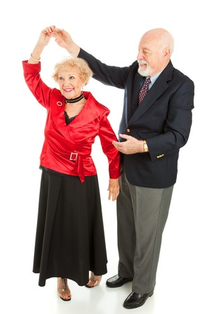 Senior man twirls his wife as they dance together.  Full body isolated on white.