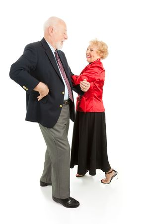 Happy senior couple having a great time square dancing.  Isolated on white.   photo