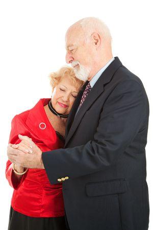 Senior couple doing a romantic slow dance.  Isolated on white.   photo