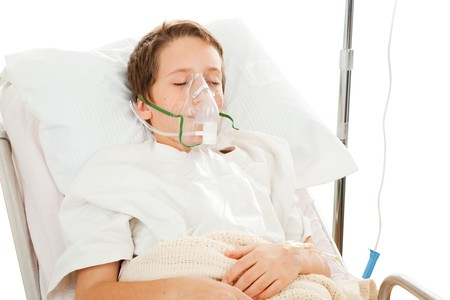 Little boy in the hospital breathing with the help of a respirator.  Isolated on white.   photo