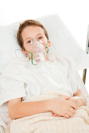 Sick little boy in the hospital breathing with an oxygen mask.   photo