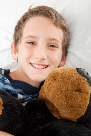 Adorable little boy, ready for bed and holding his stuffed animal.   photo