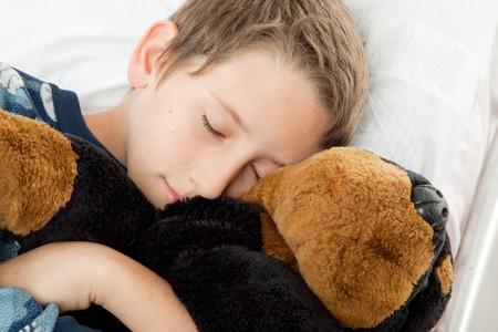 Adorable little boy sound asleep with his stuffed toy.   photo