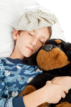 Little boy home sick in bed is sleeping with his stuffed animal. photo