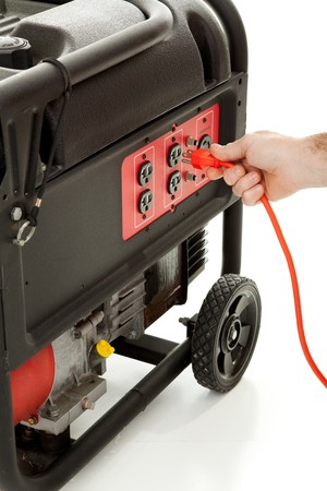 plugging: Someone plugging an extension cord into a portable gasoline generator.