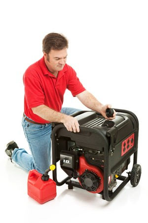 electricity generator: Man checking the fluid levels on his gas powered electricity generator.  Ready for a disaster.  Stock Photo