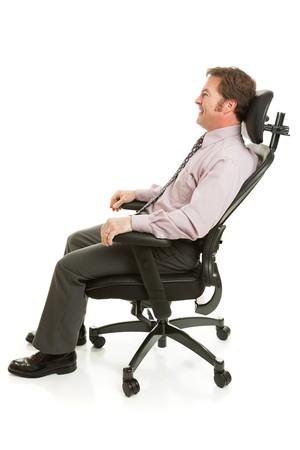 快適な人間工学的のオフィスの椅子でリラックスした実業家。フルボディの白で隔離されます。