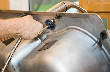 Closeup of a plumbers hand as he installs a faucet on the under side of a sink.   photo
