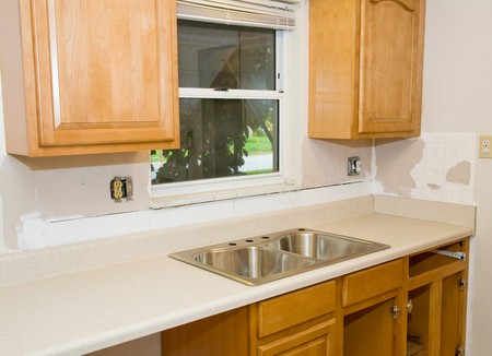 receptacle: Kitchen in the process of being remodeled.  New cabinets, counter tops, and sink are partially installed.