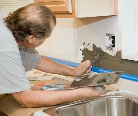 Tile setter applying mortar to drywall in preparation for tiling it.