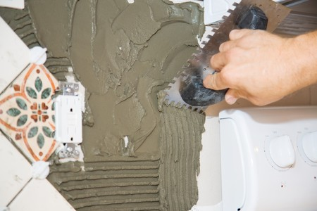 Closeup view of a tile setter scoring the mortar so tile will adhere to it.   Stock Photo