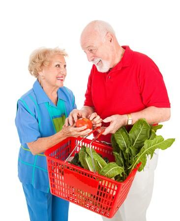 Adorable senior couple enjoys shopping for healthy fresh produce together.  Isolated on white. photo