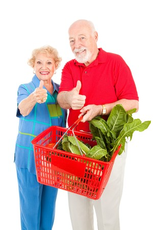 Beautiful senior couple shopping for groceries gives the thumbs up for low prices.   photo