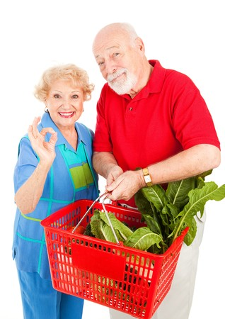 Senior couple shopping for organic produce and giving the okay sign.  Isolated on white.  Stock Photo - 4379271
