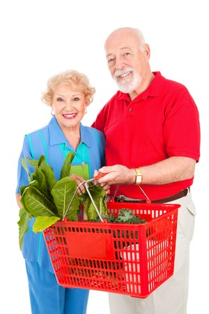 Senior couple shopping for healthy organic fruits, vegetables and soups.  Isolated on white. Stock Photo - 4379270