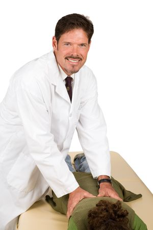 spinal adjustment: Handsome chiropractor smiles as he adjusts a patient.  Isolated on white.