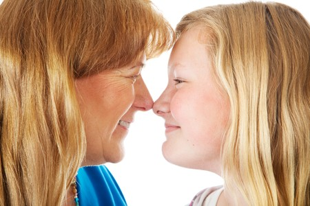 Pretty blond mother and daughter face off nose to nose.  Closeup. Stock Photo - 4443058