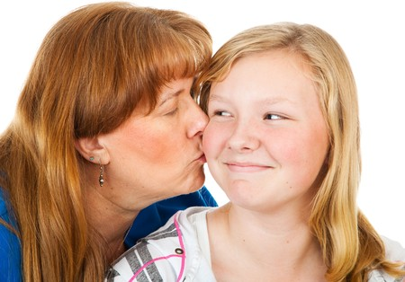 embarassed: Mother kissing her pretty blond daughter who looks embarassed.  White background. Stock Photo