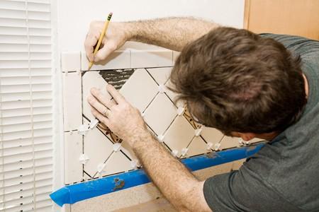 setter: Tile setter marking ceramic tiles for installation.
